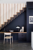 Desk with chair against a black-painted staircase wall