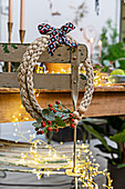 Handmade wreath of braided twine decorated with ribbon and sprigs of berries