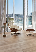 Eames Lounge Chair next to glass wall with panoramic view in living room