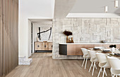 Dining table and clad wall in luxurious interior decorated in beige