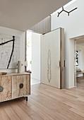 Modern, open front door in luxurious interior decorated in beige