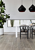 Designer chairs around dining table in front of horizontal window