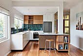 Open-plan kitchen with different fronts in white and wooden finishes