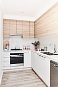 Schlichte moderne Küche mit Fronten in Weiß und Holzoptik