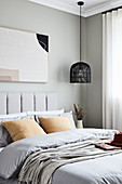 Delicate, muted shades in bedroom with pale grey walls