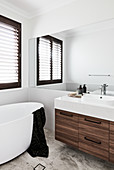 Free-standing bathtub and washstand with wooden base unit in bathroom