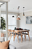 Various lamps above dining table and wooden upholstered chairs