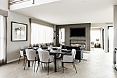 Set dining table in luxurious, open-plan interior decorated in shades of grey