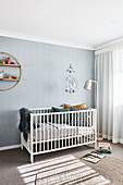 Cot against pale blue wall in minimalist nursery