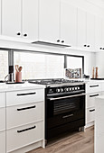 Gas cooker in classic, white kitchen with horizontal window