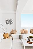 Weiße Bänke mit Bastkissen auf sommerlicher überdachter Terrasse