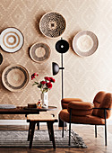 Living room with ethnic wallpaper and bast bowls as wall decoration
