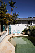Swimmingpool im Garten mit Palmen, Surfbrett am Zaun