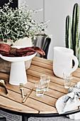 Wassergläser, Schale und Krug auf dem Gartentisch im Sommer