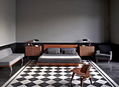 Mid-century modern furniture in masculine bedroom with chequered floor