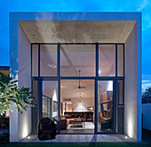 View through glass wall into cubist, architect-designed house at twilight