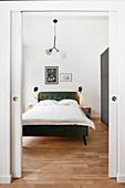 View of green bed in bedroom seen through open sliding doors