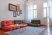 Sofa made from floor cushions and gallery of artworks in living room
