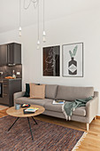 Grey sofa and kitchen cabinets in modern, open-plan interior