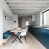 Blue base units, dining table and wood-beamed ceiling in modern, open-plan kitchen