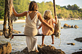 Mother and daughter on large rope swing over ocean, Thailand