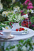 Bouquet of lilies of the valley in creamer pitcher on a tray with strawberries