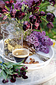 Vase of black tulips, lilac flowers and cup of espresso on tray