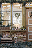 Christmas decoration with spruce branches, eucalyptus heart, mini Christmas tree, lantern, and moss boots