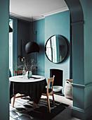 Blick durch Rundbogen-Ausschnitt auf rundne Tisch mit Stühlen in petrolfarbenem Zimmer