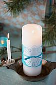 Weißer Kerze mit blauem Seidenpapier und Tortenspitze dekoriert