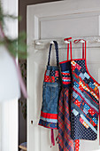 Patchwork aprons hung on door