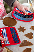 Hands hold baking tray with gingerbread cookies with pot holder