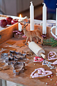 Wooden board with candles, deer figure, rolling pin, gingerbread and cookie cutters