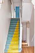 Blau und gelber Teppichboden auf Treppe in weißem Treppenhaus