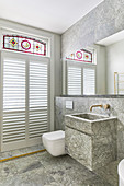 Sink next to toilet in bathroom with marble tiles, windows and stained glass elements