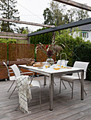 Dining table and chairs below pergola