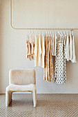 Women's clothes on rack with chair in front of it in bright interior