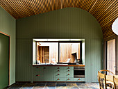 Green wood panelling and tiled floor in fitted kitchen with window