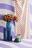 Hocker mit Blumenstrauß vor lila-weiß gestreifter Wand