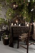 Geschirr und Windlichter auf brauner Tischdecke unter weihnachtlich dekoriert Ästen