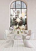 Weihnachtlich gedeckter Tisch mit Amaryllis und weiße Klassikerstühle
