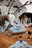 Blue-and-white soup bowls with lids and Christmas decorations on rustic wooden table