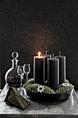 Black pillar candles, liqueur glasses and carafe in front of black wall