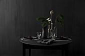 Schwarzer, gedeckter Tisch mit Lärchenzweig vor schwarzer Wand