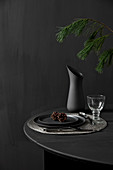 Black table set for dinner and decorated with larch branches against black wall