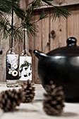 Zapfen, schwarzer Suppentopf und alte Flaschen mit Kieferenzweigen auf Tisch