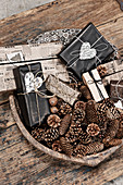 Various conifer cones and wrapped gifts in wooden bowl on rustic wooden table