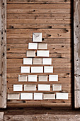 Envelopes arranged in shape of Christmas tree on rustic board wall