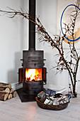 Holzofen mit brennendem Feuer, Weihnachtsgeschenke und Lärchenzweig