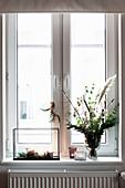 Strauß und Windlichter am Fenster